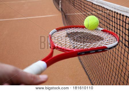 Tennis racket in hand and ball near black net on court at summer day, focus on ball