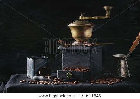 Old vintage grinder with roasted coffee beans and grind coffee in tin jar with scoop over black table with black wooden background. Dark still life