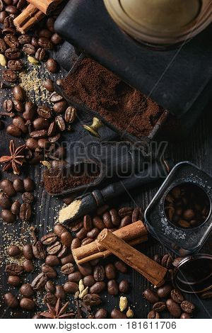 Black roasted coffee beans and grind with spices cinnamon, anise, cardamom, clove and brown sugar. With black vintage coffee grinder and scoops over wood burnt background. Top view
