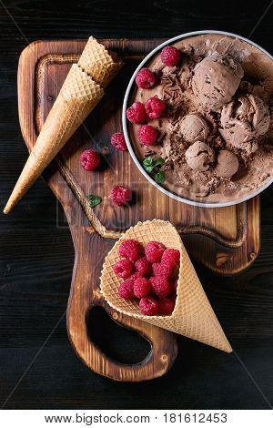Bowl of homemade chocolate ice cream with fresh raspberries, mint and waffle cone on wood serving board over black burnt wooden background. Top view with space
