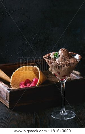 Cocktail glass with chocolate ice cream mini balls with fresh raspberries, mint and waffle cone in wood tray over black burnt wooden background. Dessert concept