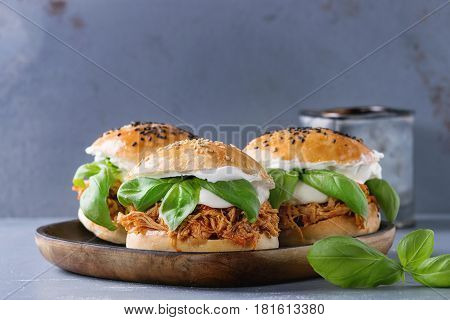 Homemade mini burgers with pulled chicken, basil, mozzarella cheese and yogurt sauce on wooden plate over gray texture background. Healthy fast food concept