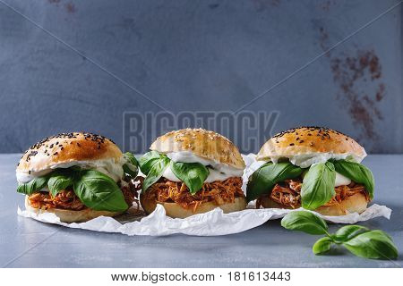 Homemade mini burgers with pulled chicken, basil, mozzarella cheese and yogurt sauce on baking paper over gray texture background. Healthy fast food concept