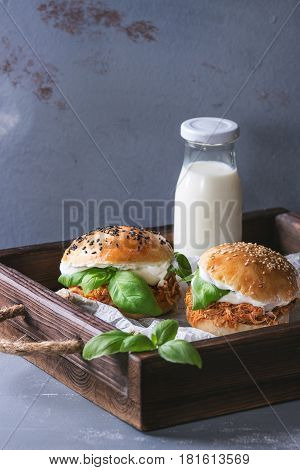Homemade mini burgers with pulled chicken, basil, mozzarella cheese and yogurt sauce on wooden tray with baking paper and bottle of milk over gray texture background. Healthy fast food concept
