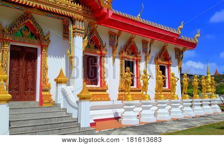 Thai Buddhist temple building with eleven gold-plated statues of Buddha lined up along the outside, on white stone pedestals, Songkhla, Thailand