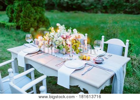 Table setting with dishes, cutler, candles and floristic. European wedding