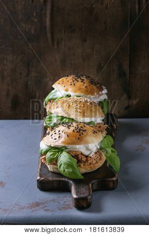Homemade mini burgers with pulled chicken, basil, mozzarella cheese and yogurt sauce on wooden serving board over gray texture background. Healthy fast food concept