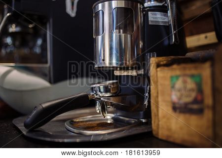 barista grinding fresh coffee into bayonet. coffee grinder in the coffee shop