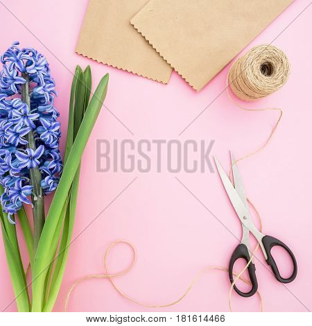 Blue hyacinth, craft paper, scissors and twine isolated on pink background. Flat lay, Top view. Woman workspace