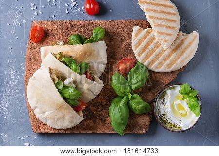 Pita bread sandwiches with grilled vegetables paprika, eggplant, tomato, basil and feta cheese served on terracotta board over gray stone background. Healthy fast food concept. Top view with space