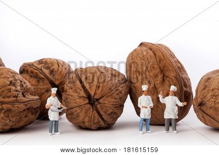 Miniature people: Chef and cooks  in front walnuts