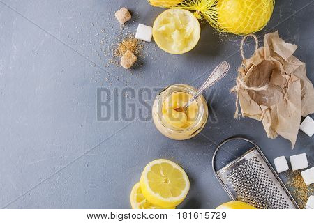 Jar of homemade lemon curd with spoon, whole and sliced lemons, sugar, grater and zest over gray blue stone texture background. Top view with space.