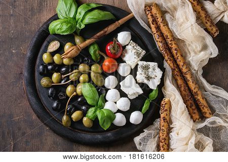 Mediterranean appetizer antipasti board with green black olives, feta cheese, mozzarella, capers, pepper, basil with grissini bread sticks over old wooden background. Top view with space