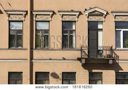 facade the exterior of the building in the classical style terracotta window balcony pigeons birds dove sitting on the ledge Sunny day