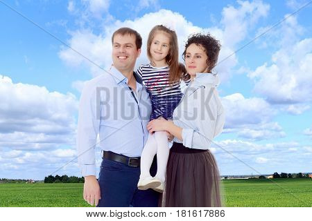 Happy young family, mom dad and little daughter.Parents keep the girl in her arms , and she hugs their neck.On the background of green grass and blue sky with clouds.