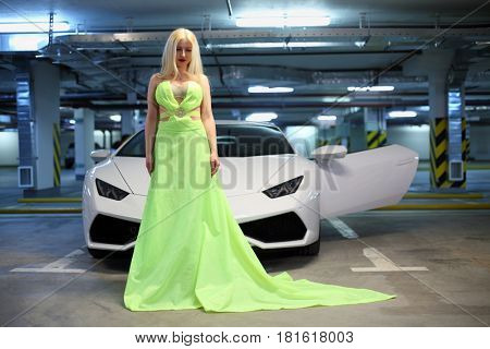 MOSCOW - MAY 20, 2016: Beautiful woman (with MR) in long dress near Lamborghini Huracan LP 610-4. Lamborghini Huracan is world first production car, using inertial navigation system