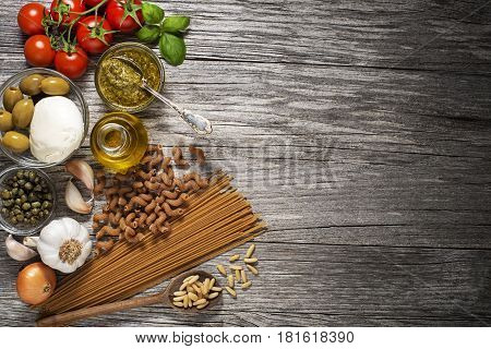 Healthy pasta with fresh ingredients on wooden background
