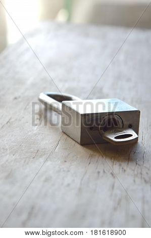 silver master key unlocked on wooden board