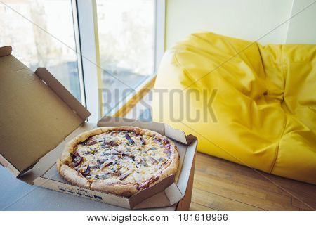 Pizza is in the office place for rest. Snack on a background seat bag.