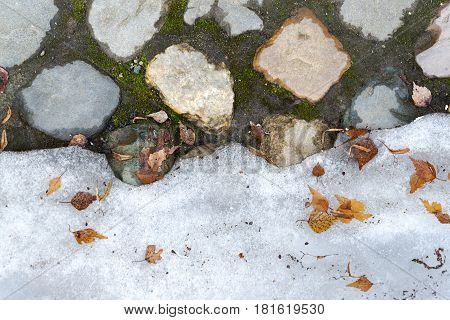 The texture of the stone and snow on the ground.
