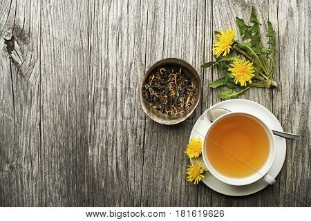 Cup of healthy dandelion tea on wooden background. Herbal medicine.