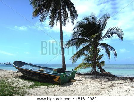 Big Corn Island Nicaragua fishing panga boat on beach with palm coconut trees Caribbean Sea Central America
