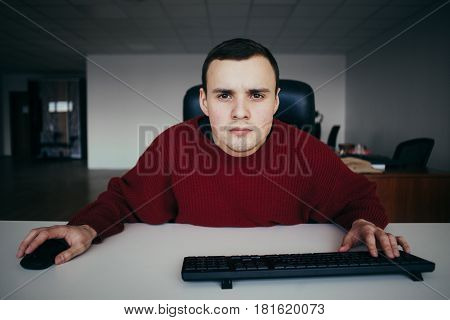 Young male office worker carefully looking at your computer monitor. Looking into the camera