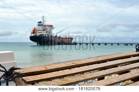 lobster pot trap with oil tanker ship at pier Picnic Center Beach Big Corn Island Nicaragua Central America