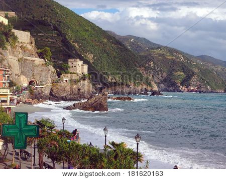 MONTEROSSO ITALY-SEPTEMBER 26: The beach waterfront and old town is seen in Cinque Terre Monterosso Italy on September 26 2016 with town of Vernazza in the distance.