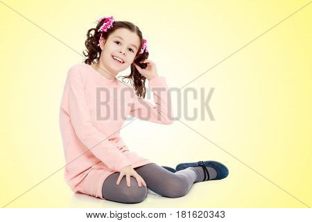 Beautiful little girl with long curly tails on the head, in which braided red ribbons . In long pink dress. The girl shyly sitting on the floor and straightens his arm hair. Close-up.