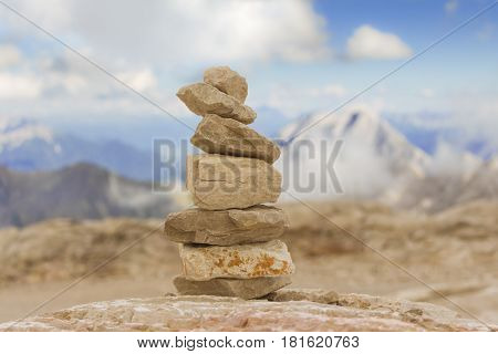 Stable stone tower in mountains show balance stability power. Stones stack in mountain panorama with blue sky visualizes creativity consulting success or showing health meditation and therapy.