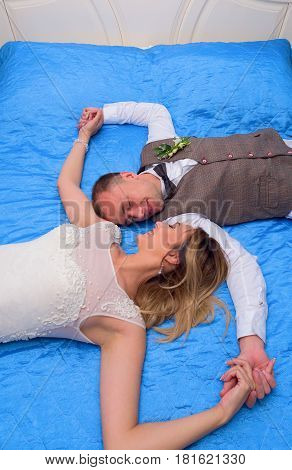 The bride and groom on the bed lovers smile