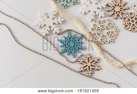 Decorative wooden snowflakes and a Christmas tree with a string of pearls and beads.