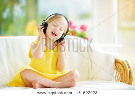 Cute Girl Wearing Huge Wireless Headphones. Pretty Child Listening To The Music. Schoolgirl Having F