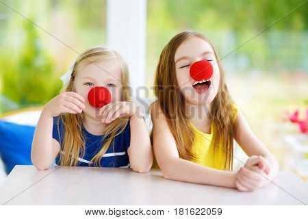 Happy Little Sisters Wearing Red Clown Noses Having Fun Together On Sunny Summer Day At Home