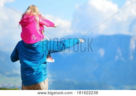 Father and his daughter admiring a view of stunning rocky Dolomites mountains of South Tyrol province of Italy Alps