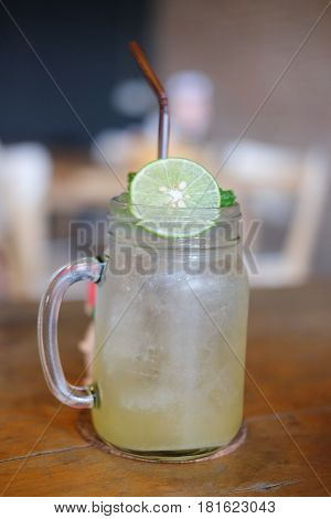 Homemade refreshing drink with lemon slices on wood table