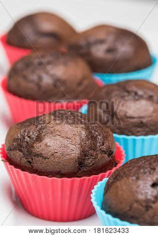 Fresh baked chocolate cupcakes in a row in silicone baking cups