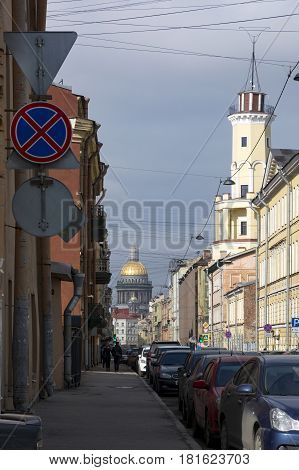 street buildings cars road view of the city of Petersburg people walking on the sidewalk away Isaac's Cathedral road signs downspouts