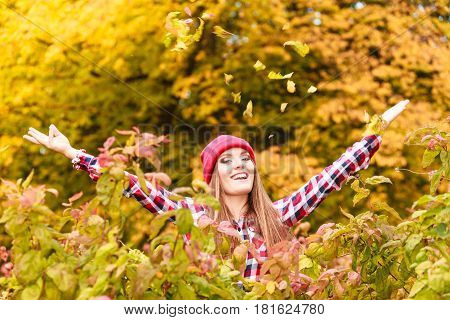 Woman In Autumn Park Throwing Leaves Up In The Air