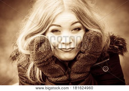Fun cheer playing forest nature outdoor concept. Girl making silly faces. Young blonde lady in winter clothing covering her face with gloves makes weird expression.