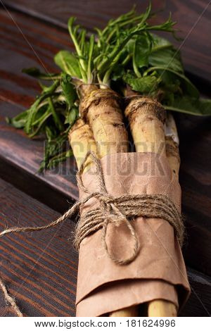 Raw Horseradish Roots On Wooden Background. Horseradish With Leaves.closeup. Selective Focus