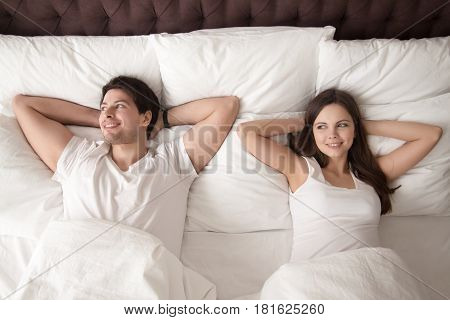 Young happy couple wearing white lying up in cozy comfortable bed hands behind the head after waking up in the morning. Married couple after wakeup, smiling, looking aside. View from above