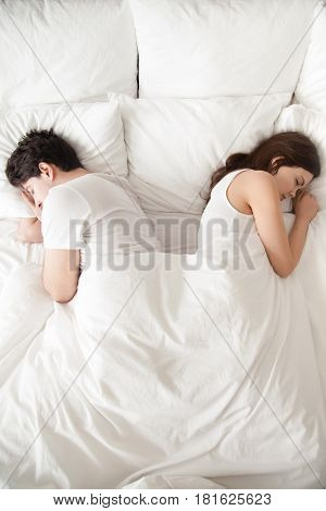Tired of disagreements, unhappy indifferent couple falling asleep back to back in bed at home. Boyfriend and girlfriend sleeping separately, having conflict and ignoring each other, sexual problems