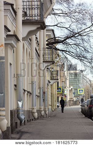man walks down a city street sidewalk buildings houses downpipes wood balcony