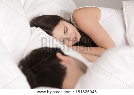Sleeping young woman resting in comfortable bed next to boyfriend, couple asleep together  in cozy bed covering with blanket, see pleasant dreams, napping in the morning before waking up