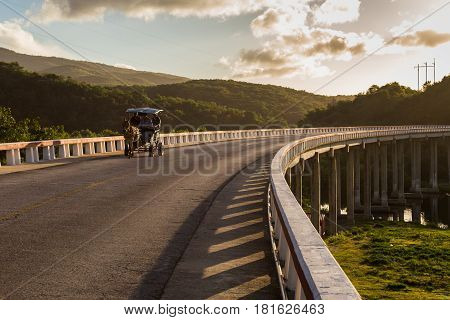 A typically rural scene in Cuba - if people aren't being ferried around in classical cars from the 1950's then invariably it's by horse & cart. Here I've captured one crossing a curved bridge spanning an river estuary which spills out into Caribbean sea.
