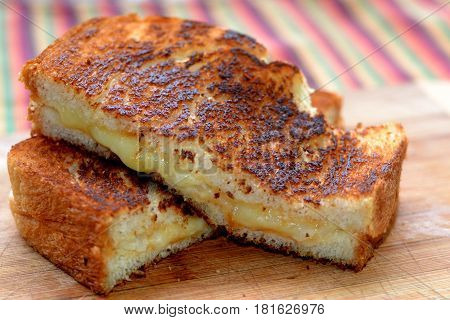 Grilled Cheese Sandwhich with White Cheddar Cheese: Close-up, side view, focus on foreground.