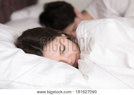 Couple having a restful sleep, young pretty lady lying on pillow under covering in comfortable white bed, looking peaceful and serene, soft healthy sleep on weekend and good dreams