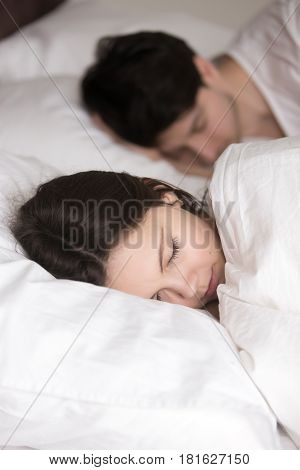 Happy couple sleeping in a big comfortable bed at home or hotel, resting on white soft linen, late risers loving to sleep, do not want to wake up, sleeping woman looking rested, having pleasant dream